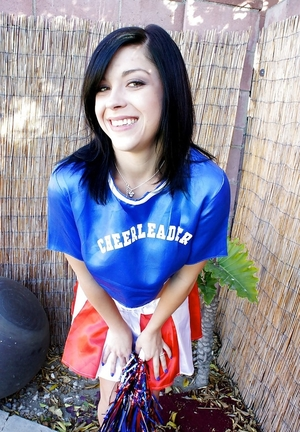Black-haired cheerleader goes outdoors to perform individual strip show in backyard