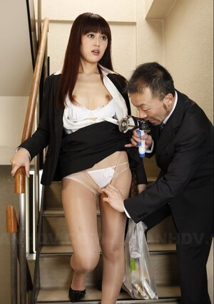 Fella in a suit takes off Asian's nylons on the stairs and also aims strange toy at it