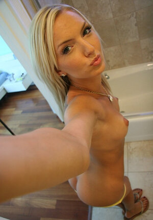 Skinny blonde seductively poses on camera during solo fun in bathroom