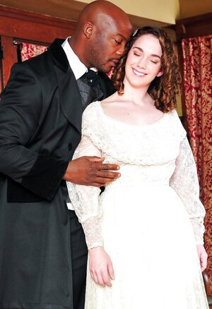 Pale-skinned broad in old-fashioned white dress kisses black dude in a suit