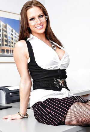 Big-breasted office dame gets on the desk and strips to sexy black underwear