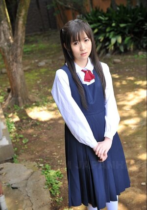 Innocent Japanese schoolgirl with nice-looking eyes walks seductively under sun