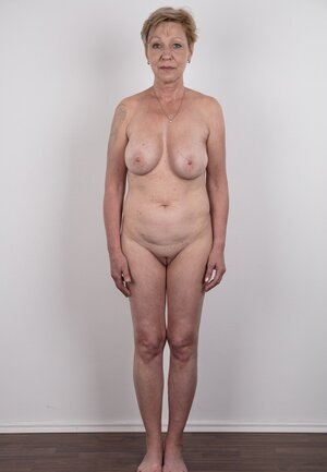 Aged porn model with tattooed shoulder advertises natural twins and slit