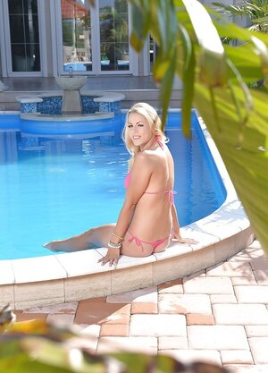 Young and fresh whore in erotic bikini has hole penetrated by own fingers poolside